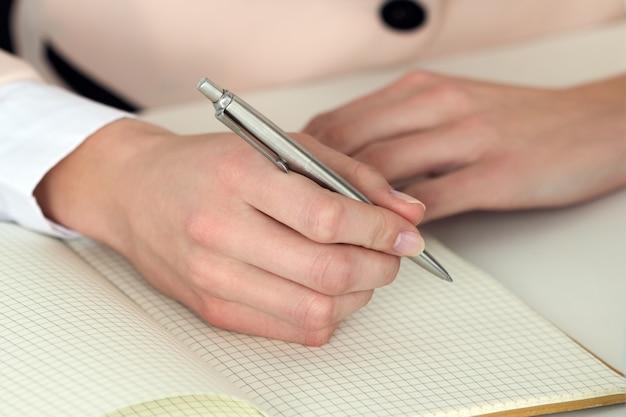 Main de femme tenant un stylo argenté prêt à prendre note dans un cahier ouvert. femme d'affaires ou employé sur le lieu de travail, rédaction d'idées commerciales, de plans, de tâches à l'organisateur personnel.