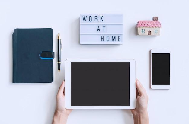 Main de femme tenant la tablette sur un bureau blanc avec agenda, smartphone et travail à la maison mot sur lightbox