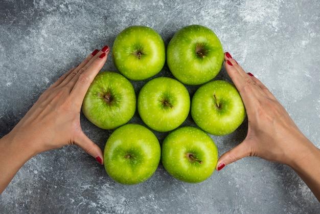 Main de femme tenant un tas de pommes sur marbre.