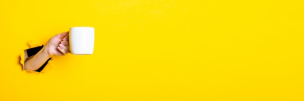 Main de femme tenant une tasse blanche sur fond jaune vif