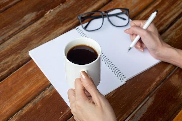 Main de femme tenant une tasse de café avec café noir et verre à œil écriture cahier vierge.
