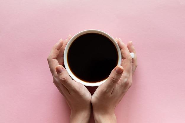 Main de femme tenant une tasse de café sur fond rose, mise à plat, vue de dessus