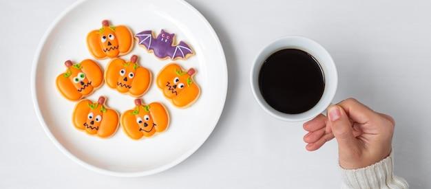 Main de femme tenant une tasse de café en mangeant des biscuits d'halloween drôles. joyeux halloween, astuce ou menace, bonjour octobre, automne automne, concept traditionnel, fête et vacances