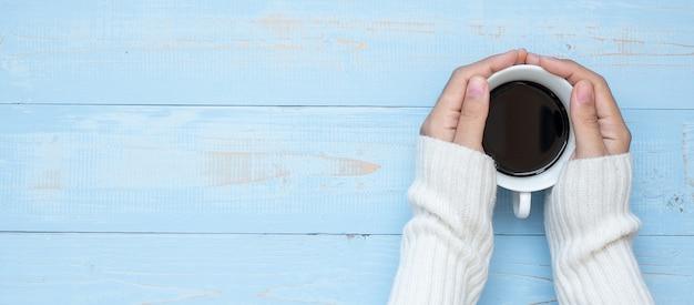 Main de femme tenant une tasse de café noir fond en bois bleu