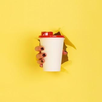 Main femme tenant une tasse de papier blanc sur fond jaune.