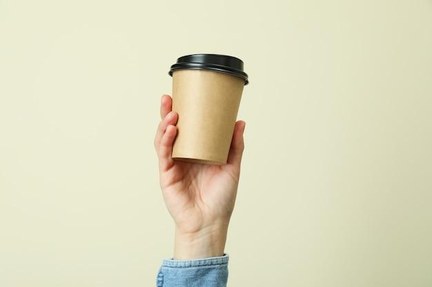 Main de femme tenant une tasse de papier sur fond beige