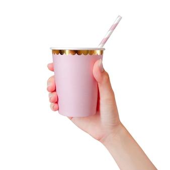 Main de femme tenant une tasse de papier rose avec des pailles isolé sur fond blanc.