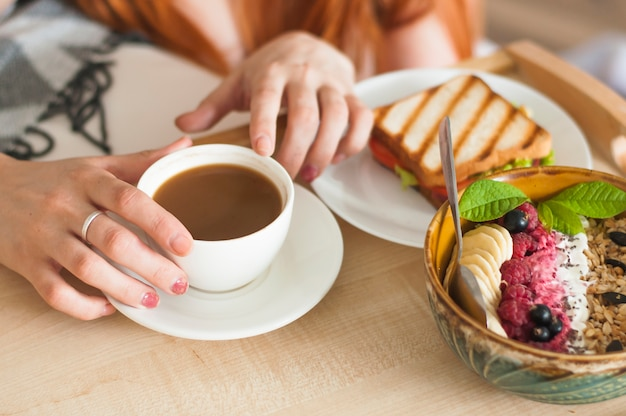 Main de femme tenant une tasse de thé avec sandwich et petit-déjeuner à l'avoine