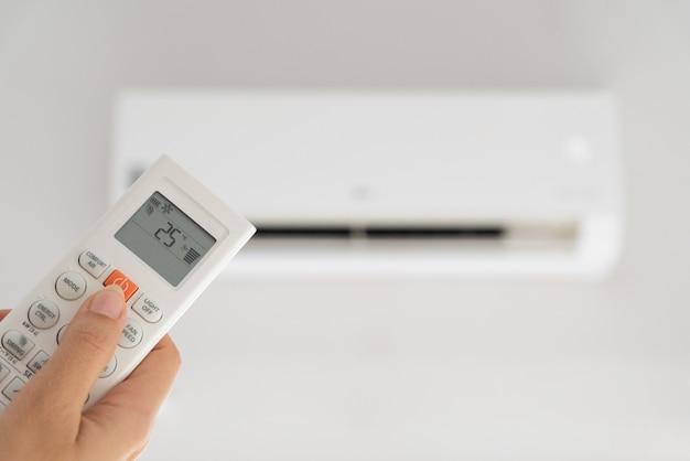 Main de femme tenant la télécommande dirigée sur le climatiseur