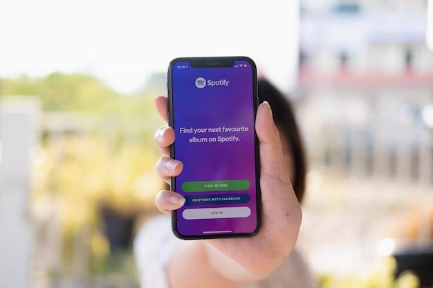 Main de femme tenant un téléphone avec écran de connexion.