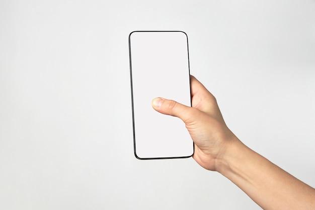 Main de femme tenant le téléphone sur fond blanc avec espace de copie. femme tenant un smartphone avec écran blanc.