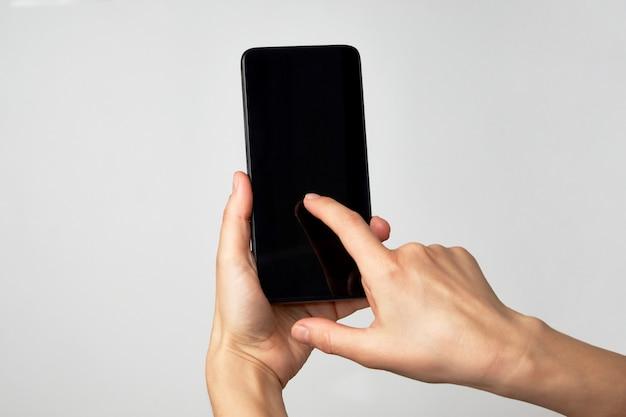 Main de femme tenant le téléphone sur fond blanc avec espace copie