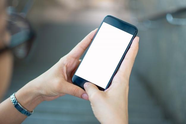 Main de femme tenant un téléphone intelligent avec l'arrière-plan flou. mise au point sélective et mise au point douce.