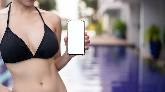 Main de femme tenant un téléphone mobile avec une maquette d'écran blanc vierge au bord de la piscine.