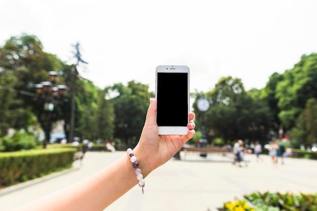 Main de femme tenant le téléphone portable à l'extérieur