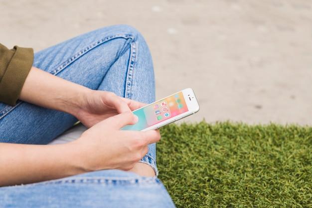 Main de femme tenant le téléphone portable en utilisant l'application de médias sociaux