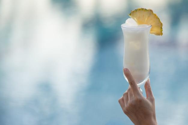 Main de femme tenant un verre de cocktail au bord de la piscine.