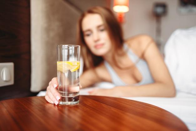 Main de femme tenant un verre avec de l'eau citronnée, se réveiller. bon matin sain dans la chambre