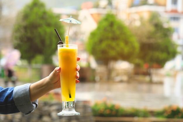 Main de femme tenant un verre de jus d'ananas frais, concept de jus de désintoxication