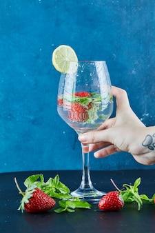 Main de femme tenant un verre de jus avec des fruits entiers et de la menthe à l'intérieur