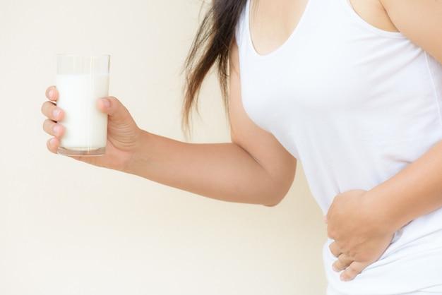 Main de femme tenant un verre de lait ayant mal au ventre.