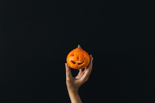 Main de femme tenir la citrouille d'halloween sur une surface noire