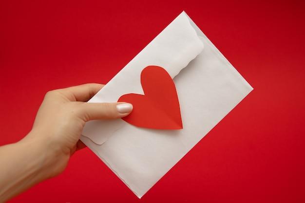 Main de femme tenir enveloppe scellée avec amour en forme de coeur rouge. concept de la saint-valentin