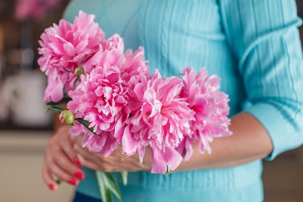 Main de femme tenir la fleur de pivoine blanche.