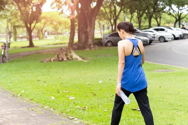 Main femme tenue bouteille eau marche dans parc