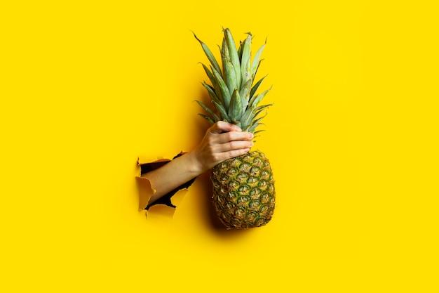 La main de femme tient un ananas mûr entier dans un fond de carton jaune déchiré