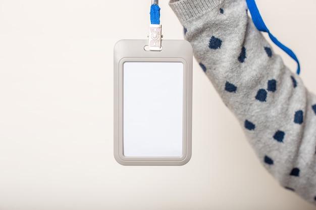 La main de la femme tient un badge, une étiquette de nom, un identifiant d'étiquette de nom, une lanière sur un mur léger