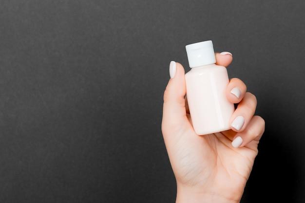 La main de la femme tient une bouteille de cosmétiques sur fond noir avec un espace de copie pour votre conception.
