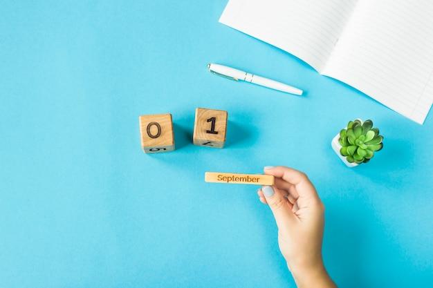 Une main de femme tient un calendrier en bois avec la date du 1er septembre