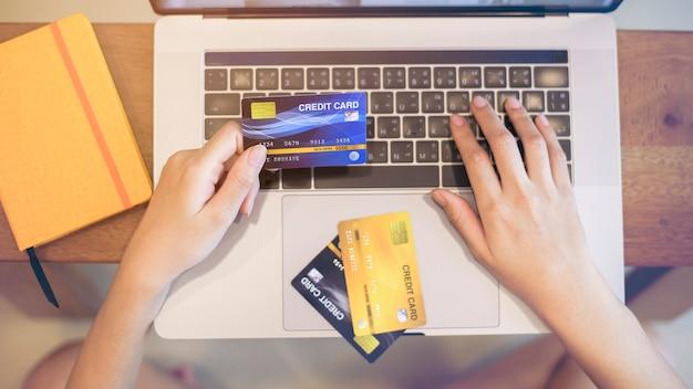 Main de femme tient une carte de crédit, shopping en ligne