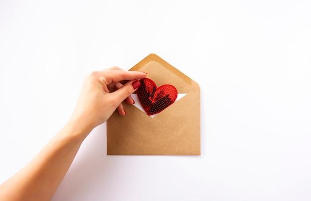 Une main de femme tient un coeur rouge dans une enveloppe brune
