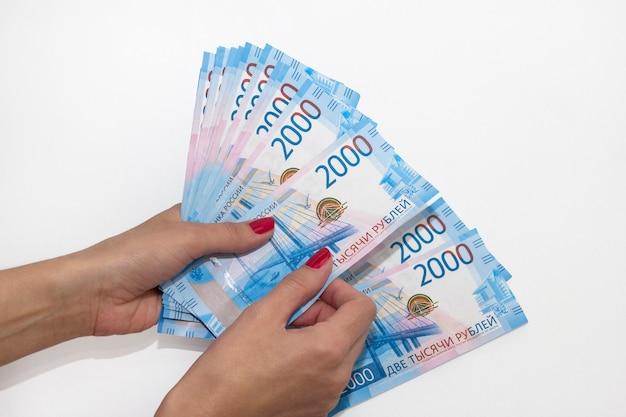 La main d'une femme tient du papier-monnaie. rouble russe