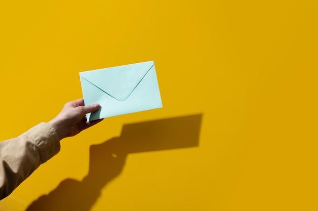 Main de femme tient une enveloppe bleue sur une surface jaune