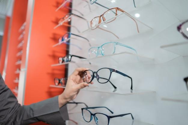 La main d'une femme tient une paire de lunettes collée à une fenêtre dans la clinique ophtalmologique