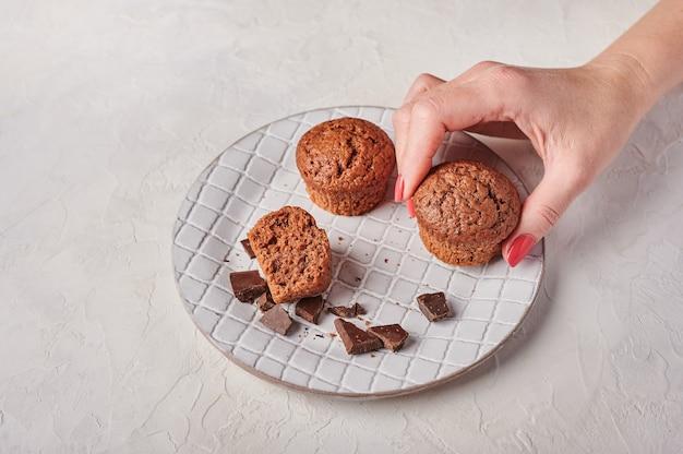 La main de la femme tient un petit gâteau et d'autres morceaux de chocolat en plaque texturée sur la lumière en bois