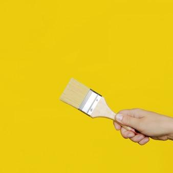 La main de la femme tient un pinceau propre sur un mur jaune vif.