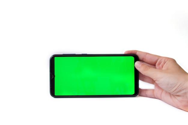 La main de la femme tient le smartphone en position horizontale avec un écran vert sur fond blanc, incrustation de chrominance, maquette.