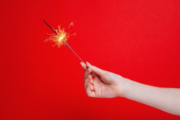 Une main de femme tient un sparkler sur rouge
