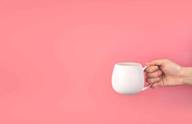 Une main de femme tient une tasse blanche sur fond rose