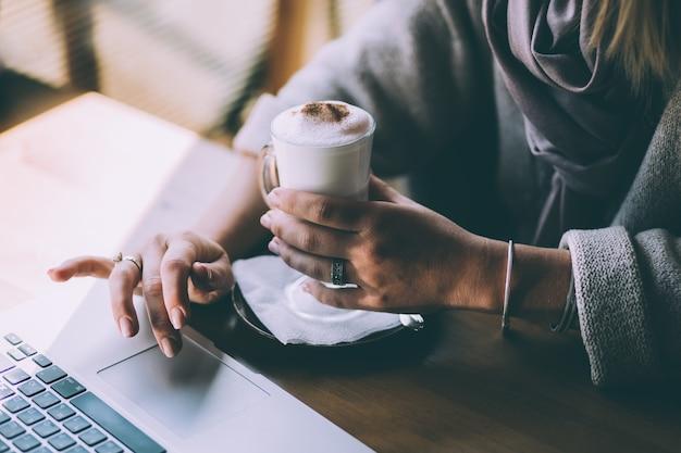 La main d'une femme tient une tasse de café et appuie sur les touches de l'ordinateur portable avec l'autre main
