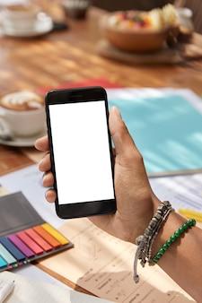 La main de la femme tient un téléphone portable moderne avec écran blanc