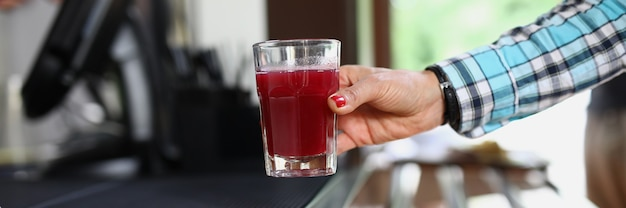 La main de la femme tient le verre au café avec un liquide rouge semblable à une boisson aux fruits ou à de la gelée
