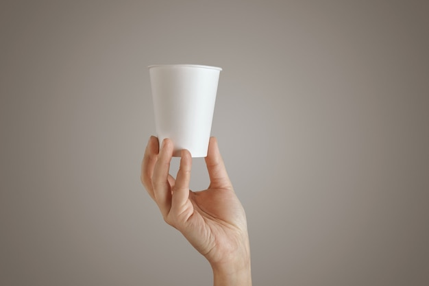 Main de femme tient le verre de papier à emporter vide vide du bas, présentation au centre, vue latérale, isolé, méconnaissable