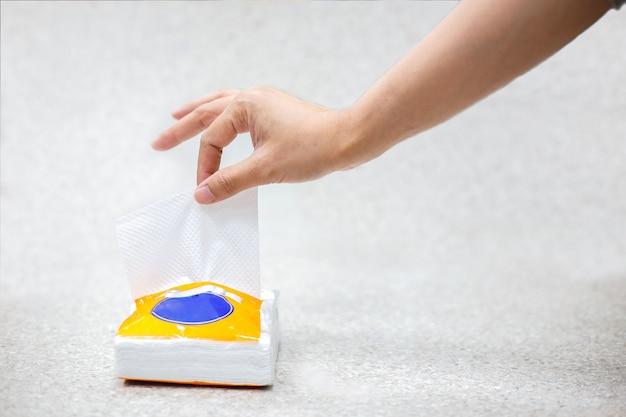 Main de femme tirant du papier de soie blanc de la boîte de mouchoirs pour nettoyer quelque chose sur une surface grise.