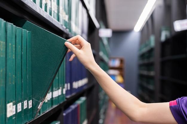 Main de femme tirant un livre de thèse sur l'étagère de la bibliothèque. livres de couleurs vertes.