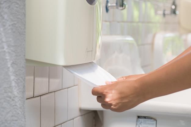 Main de femme tirant un tissu blanc de la boîte de tissu dans les toilettes.